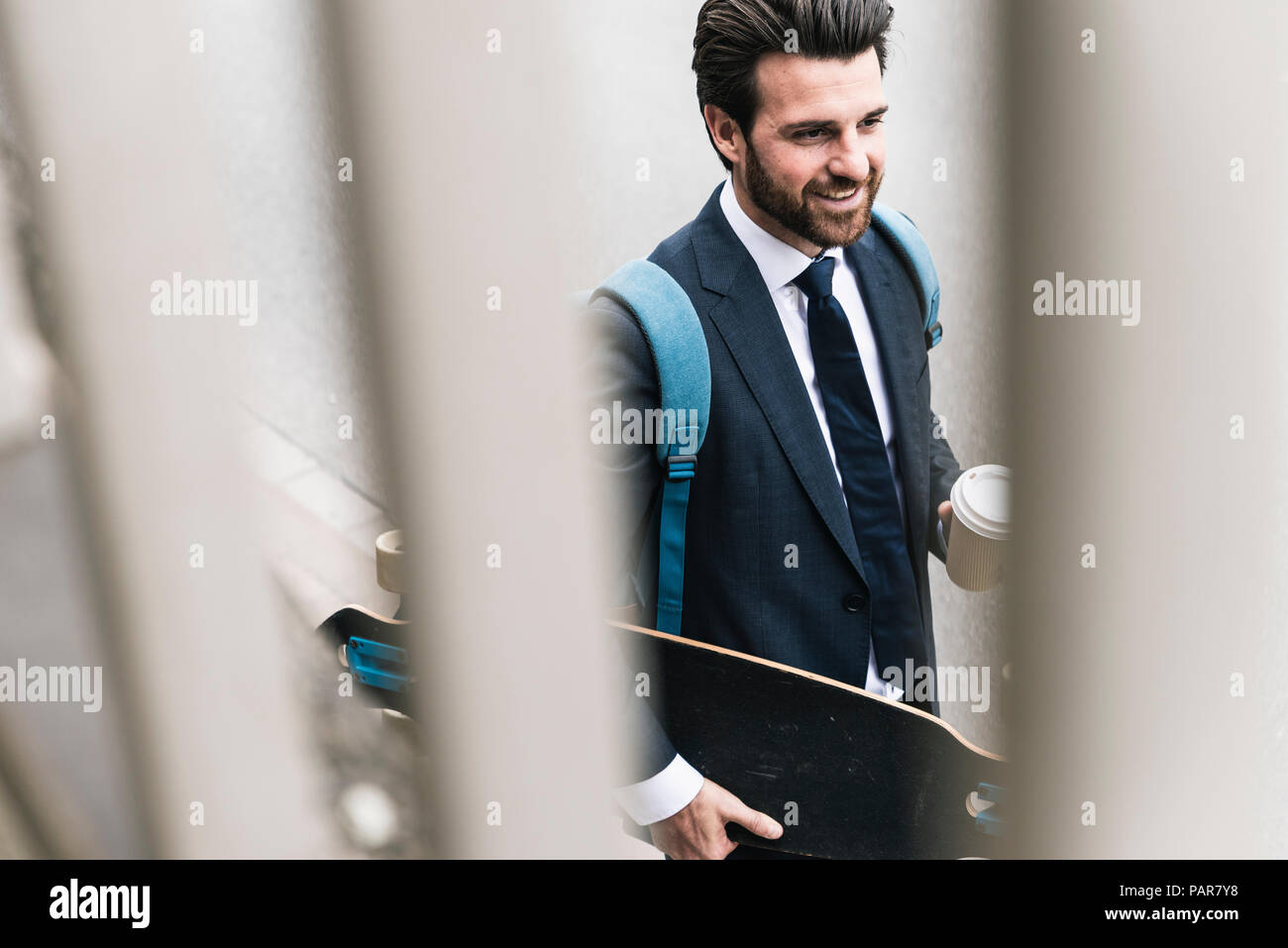 Smiling businessman with takeaway coffee and skateboard walking outdoors - Stock Image