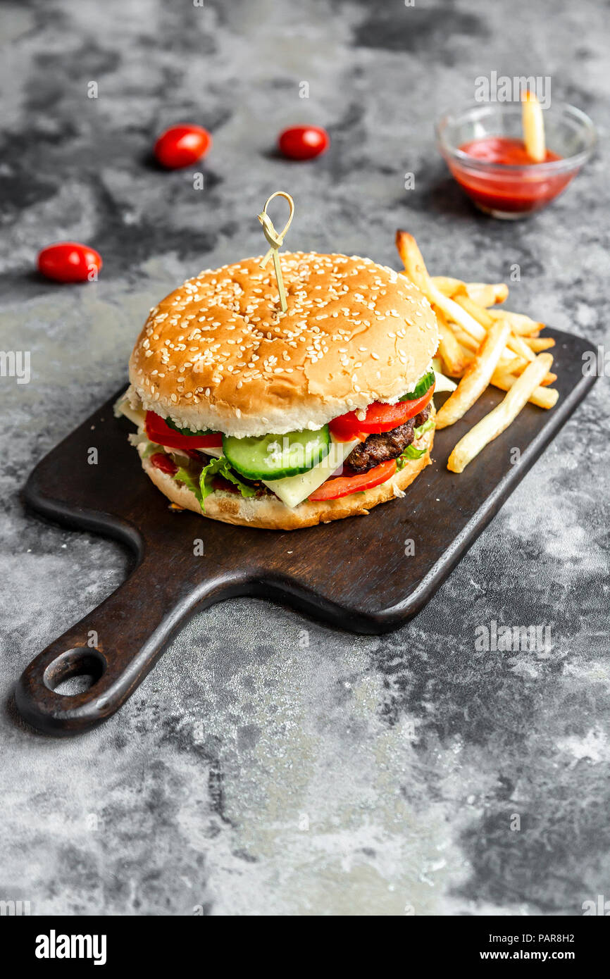 Homemade Hamburger with cheese, french fries, ketchup and tomato - Stock Image