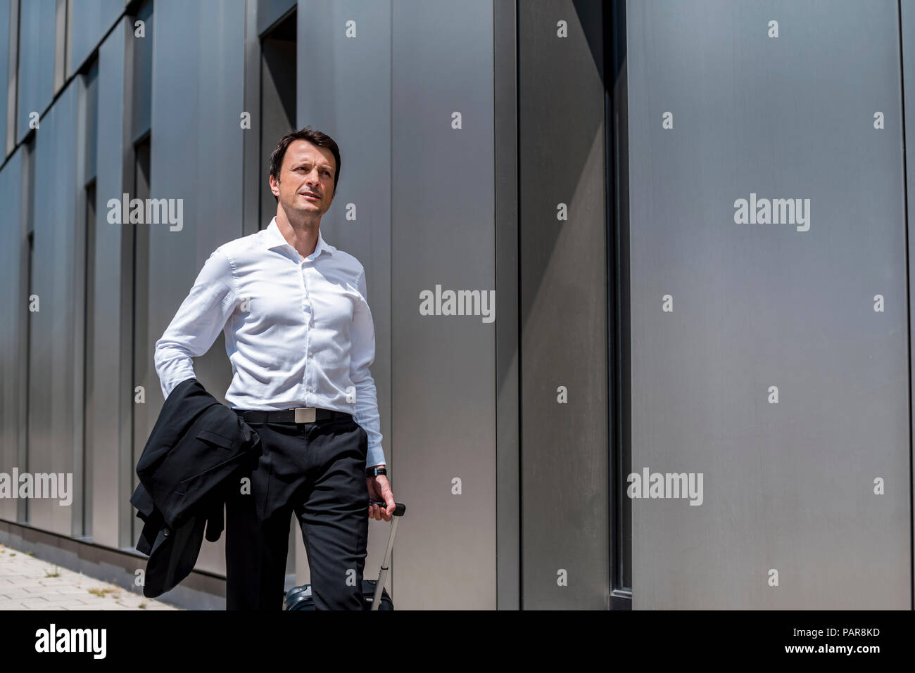 Businessman with rolling suitcase walking in the city Stock Photo
