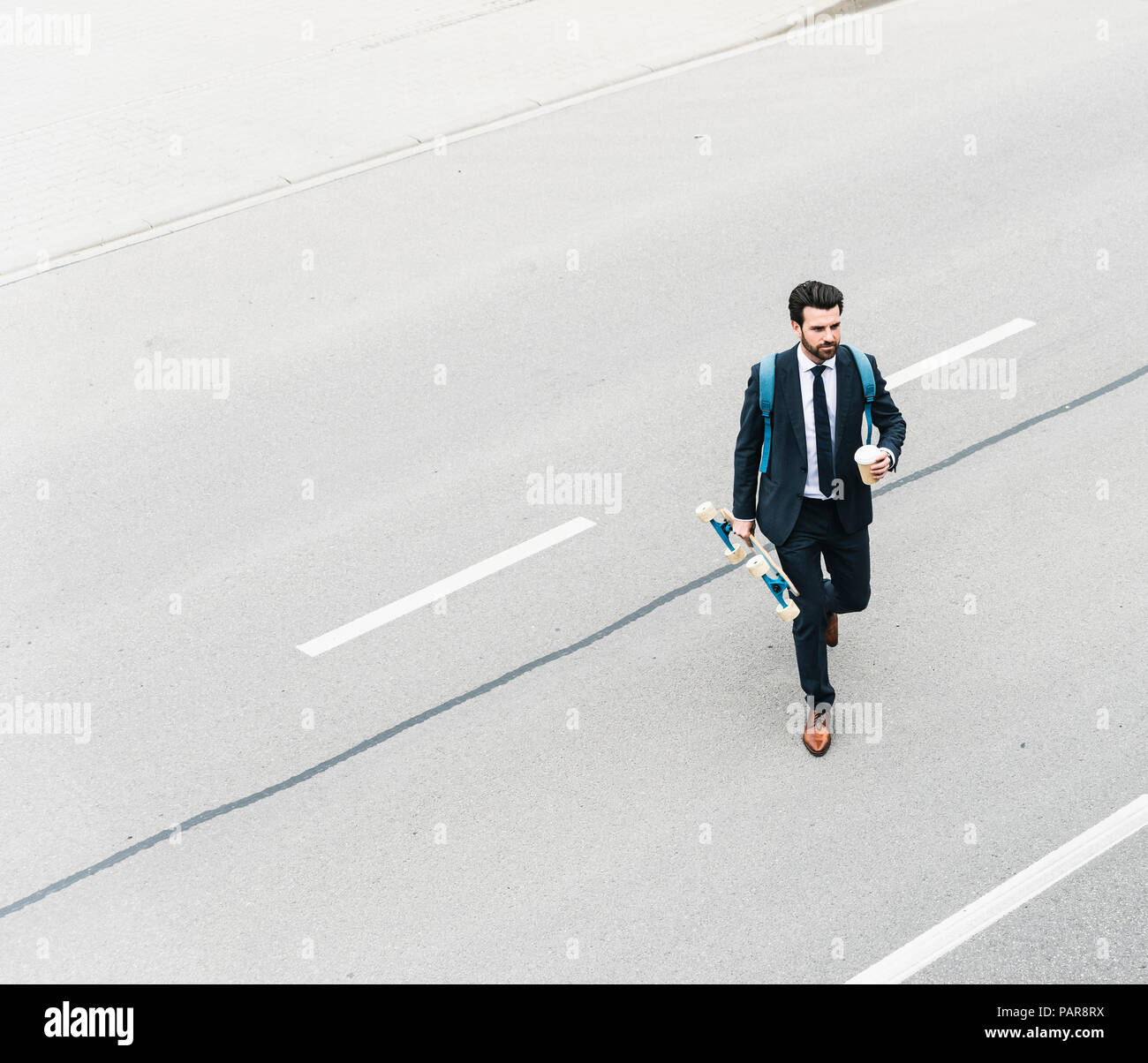 Businessman with takeaway coffee and skateboard walking on the street - Stock Image