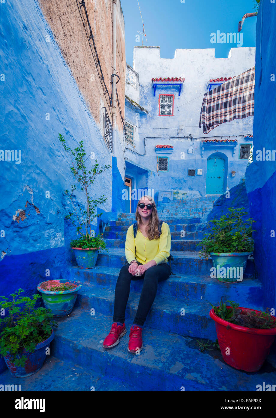 Young woman sits on stairs in the old town, blue house facades, medina of Chefchaouen, Chaouen, Tangier-Tétouan, Morocco Stock Photo