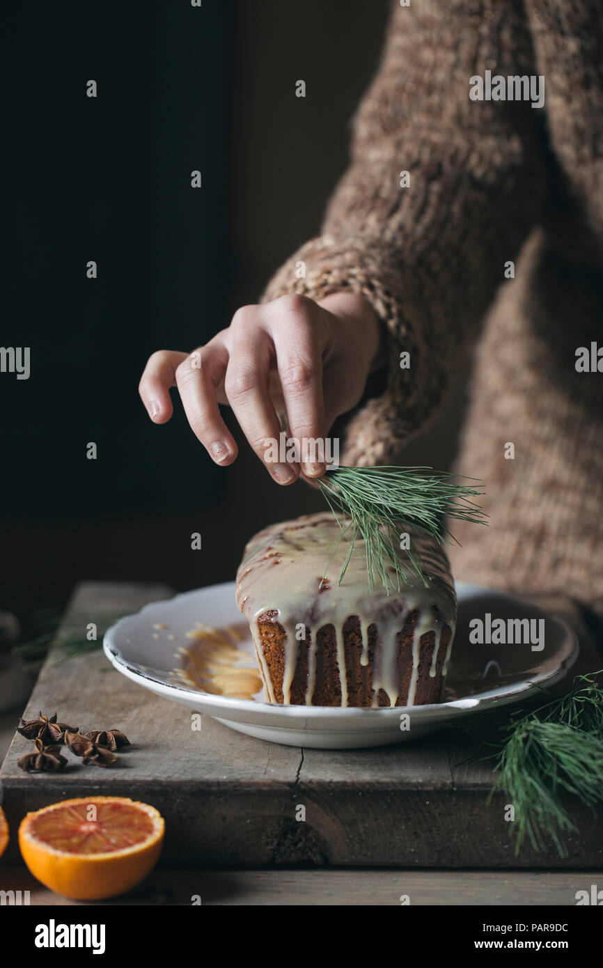 Woman's hands decorating Christmas cake - Stock Image