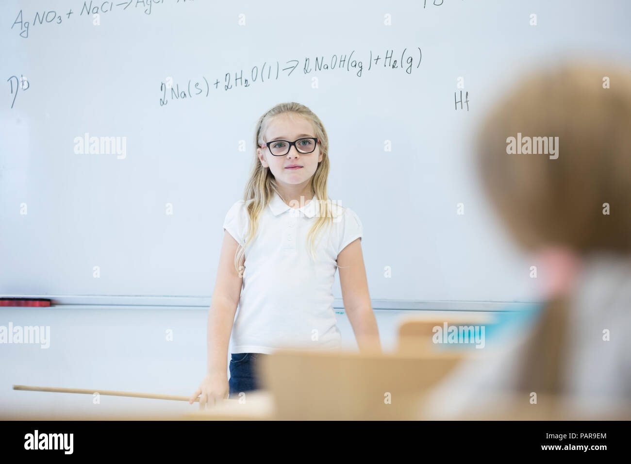 Schoolgirl standing at whiteboard with formula in class - Stock Image