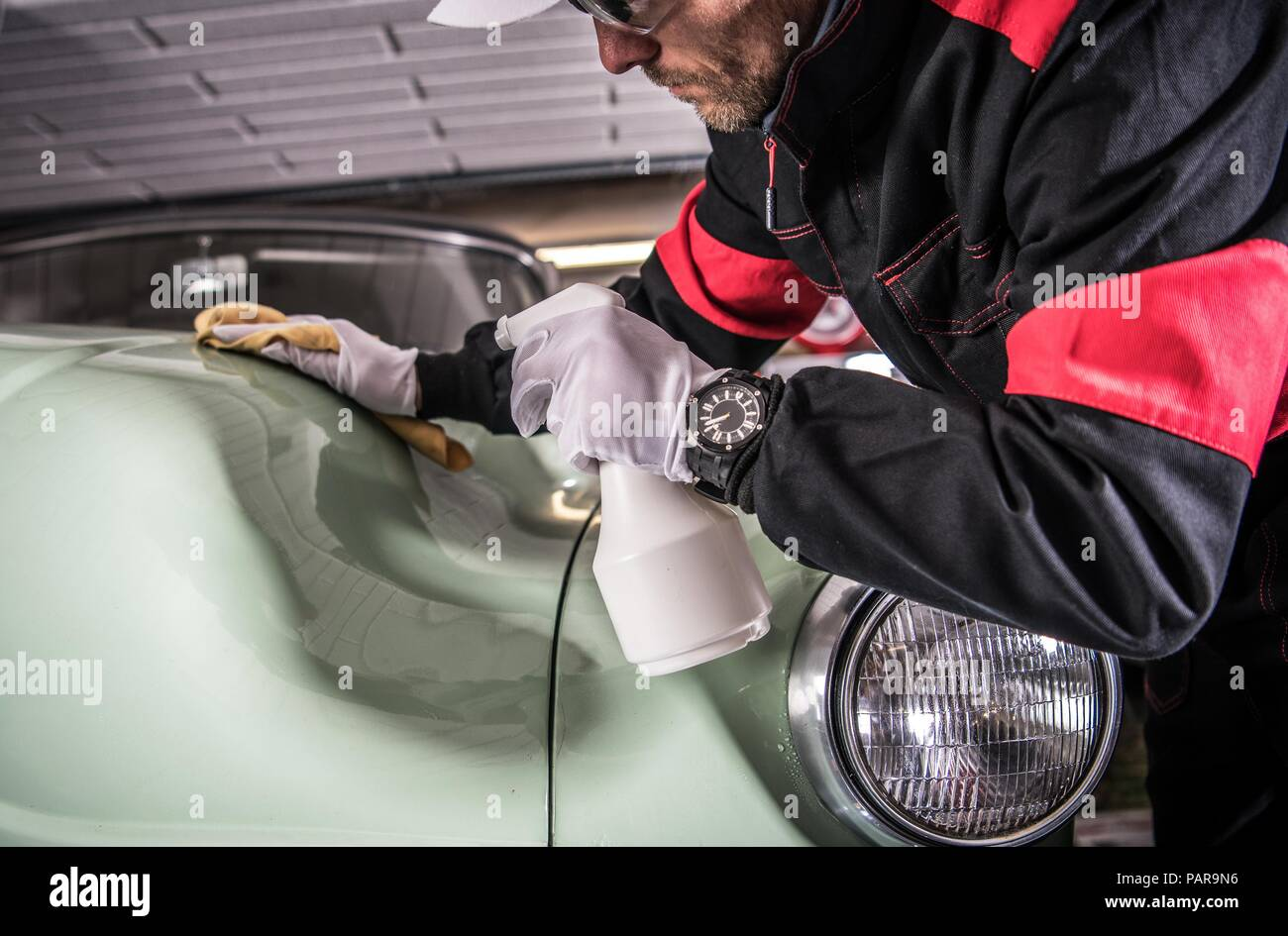 Men Cleaning His Car Body Using Professional Cleaner in Liquid. Vehicle Washing and Detailing Theme. Classic Car. - Stock Image