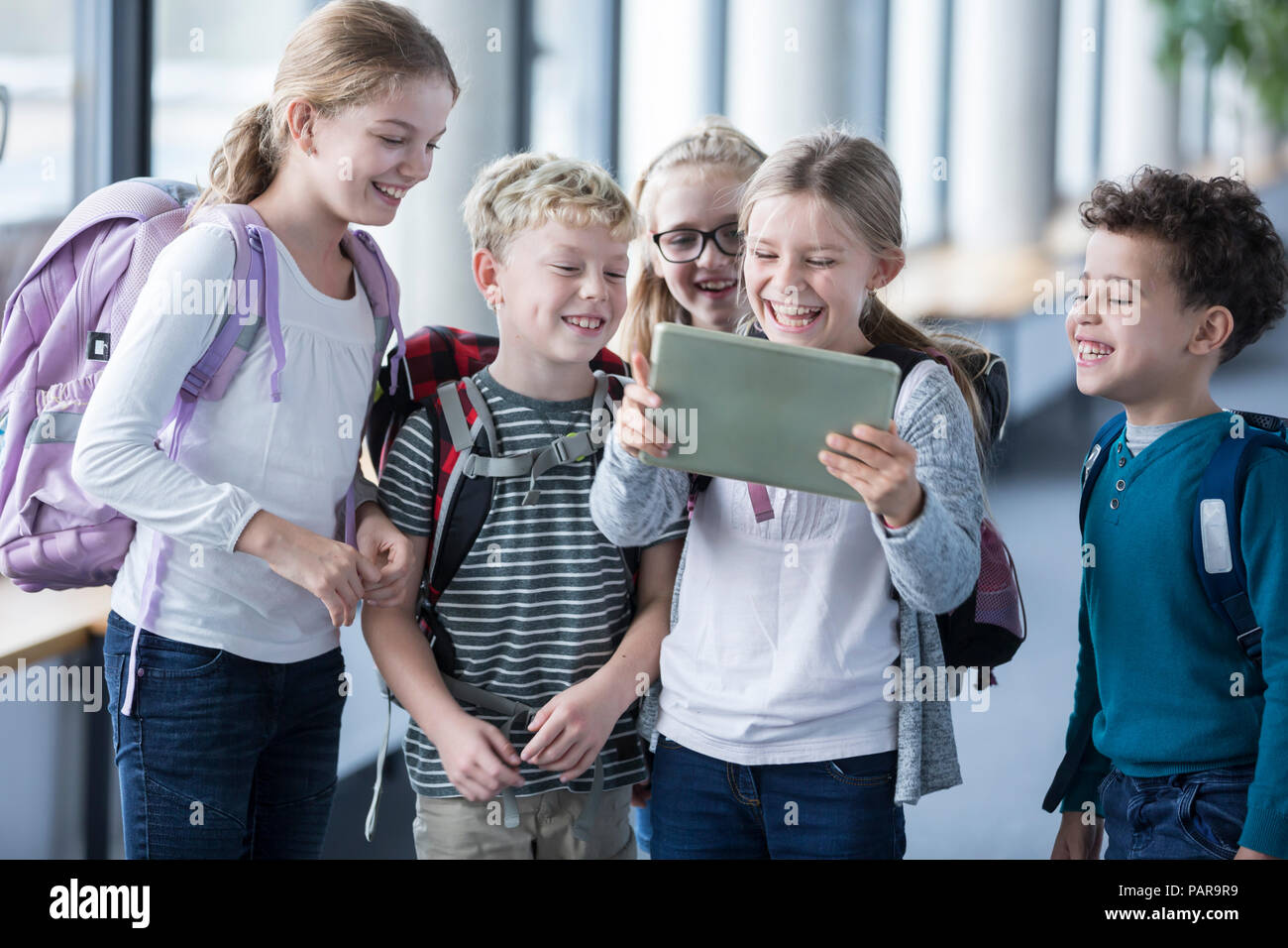 Laughing pupils looking at tablet on school corridor - Stock Image