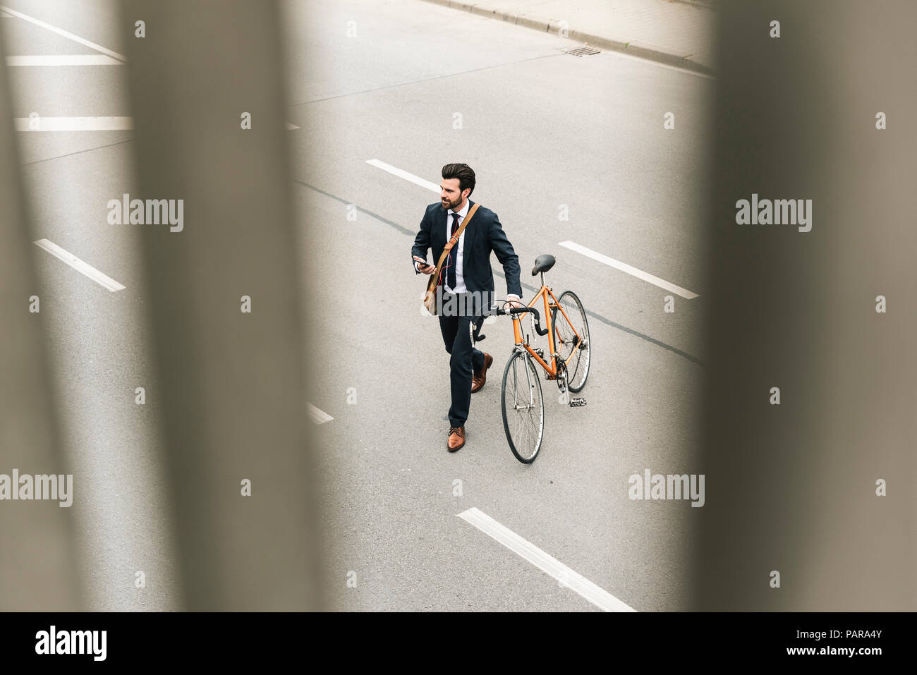 Businessman with bicycle and cell phone walking on the street - Stock Image