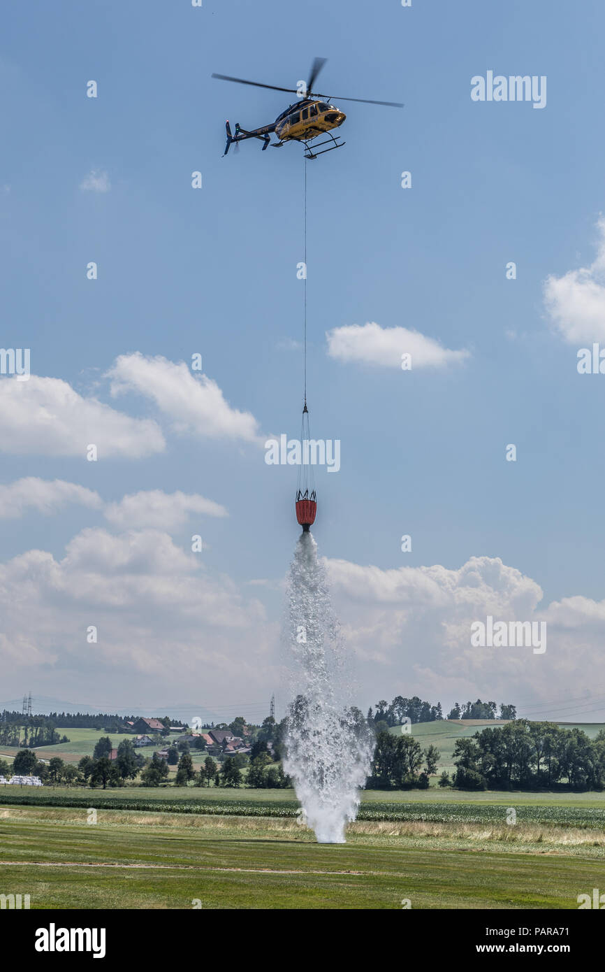 Helicopter empties water tank for precise fire extinguishing, exercise, Switzerland - Stock Image