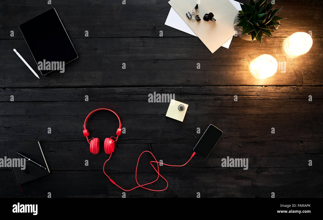 Red headphones streaming music from smartphone, lying on desk - Stock Image