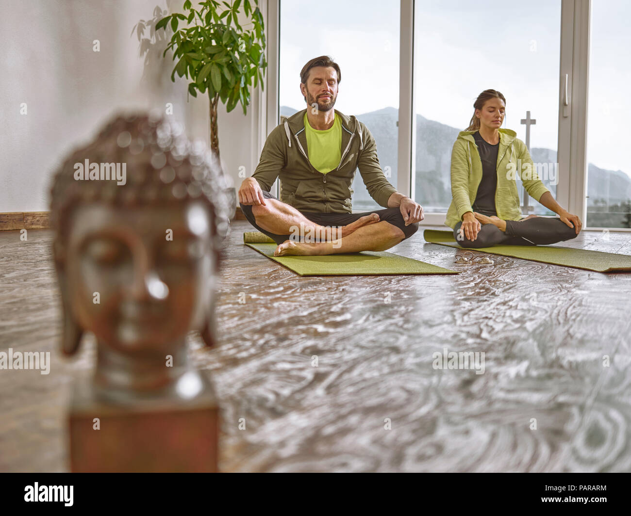 Couple practicing yoga in a room with panorama window - Stock Image