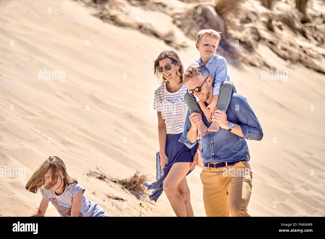 Happy family walking on the beach together - Stock Image