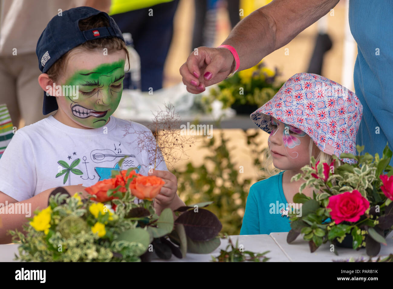 Children with painted faces flower arranging at a country fair in Hampshire - Stock Image