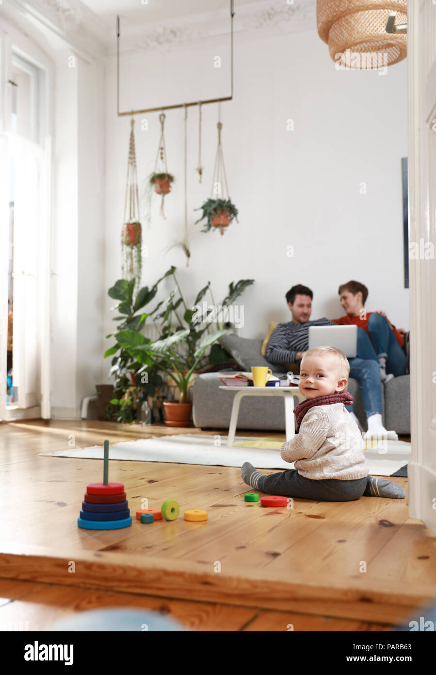 Parents sitting on couch, using laptop, while daughter is playing on the floor Stock Photo