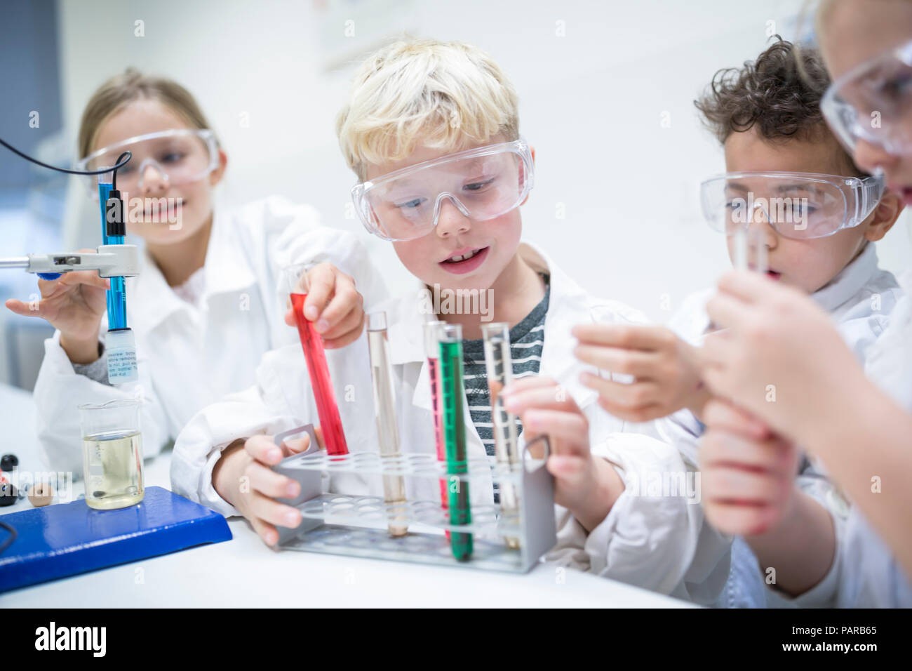 Pupils in science class experimenting with liquids in test tubes - Stock Image