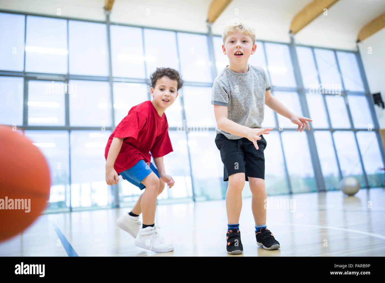 Two schoolboys playing basketball in gym class - Stock Image