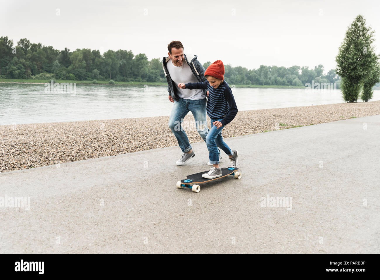 Happy father running next to son on skateboard at the riverside - Stock Image