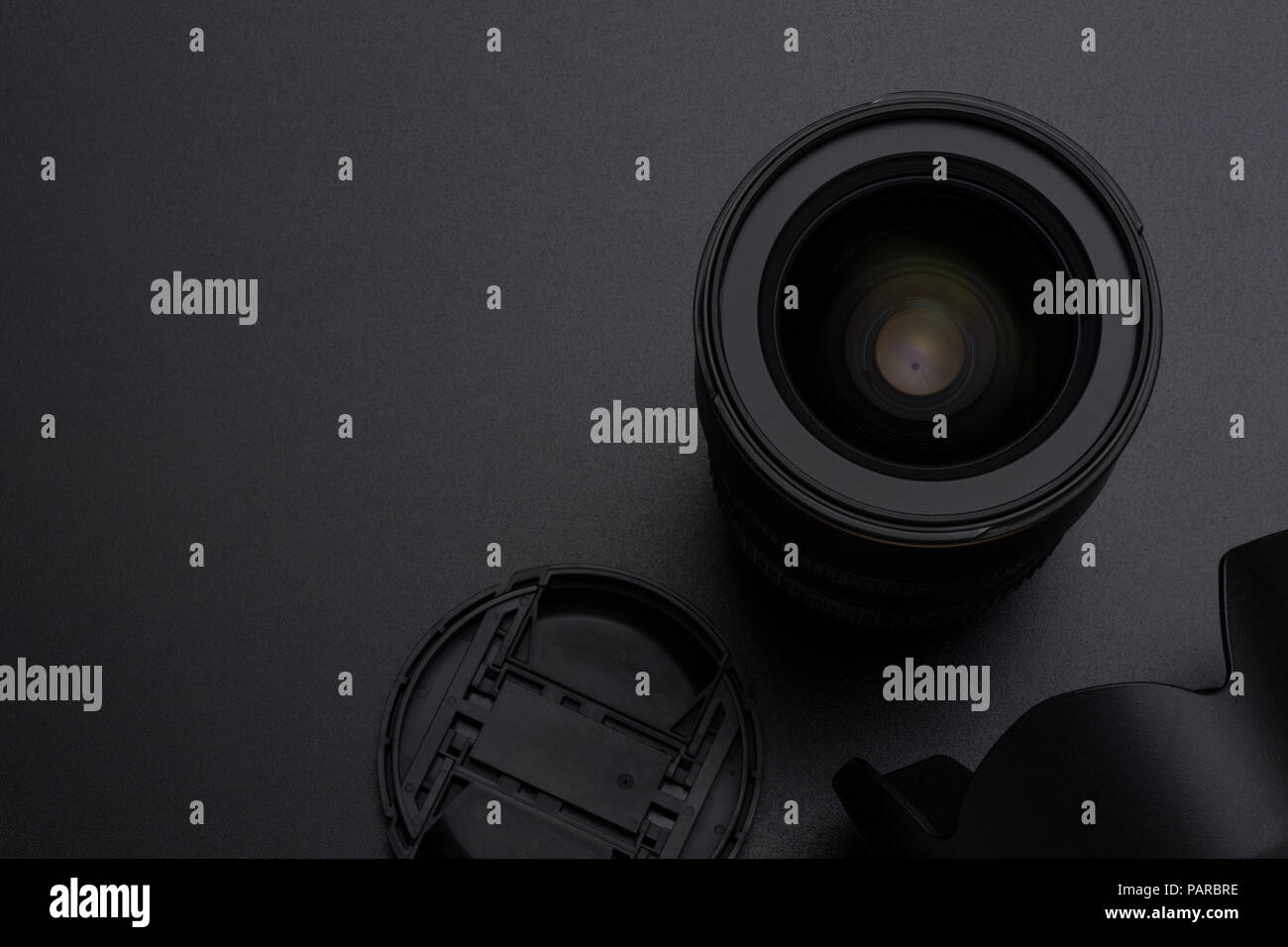 Photo DSLR camera or video lens, hood and front cap close-up image on black background - Stock Image