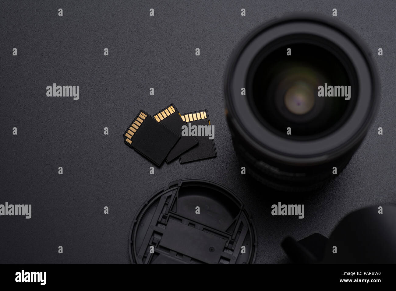 Photo DSLR camera or video lens, SD memory cards, hood and front cap close-up image on black background - Stock Image