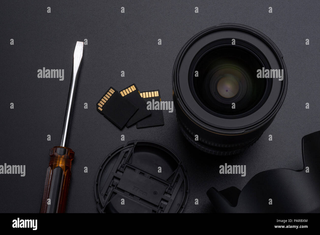 Photo DSLR camera or video lens, SD memory cards, hood, screwdriver and front cap close-up image on black background - Stock Image