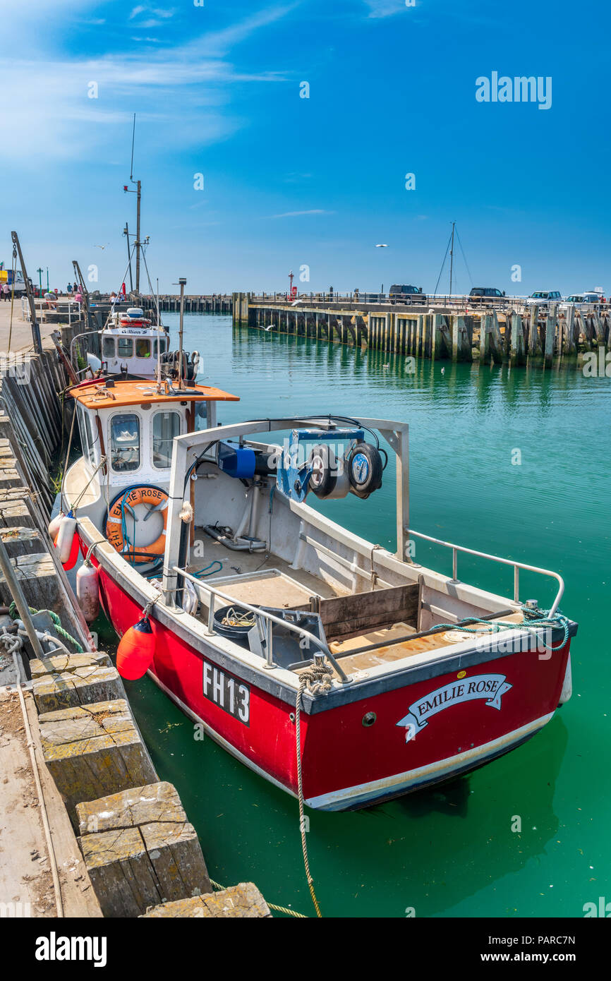 A small fishing boat waits at the quayside to unload its catch in the aqua green waters of West Bay in Dorset. - Stock Image