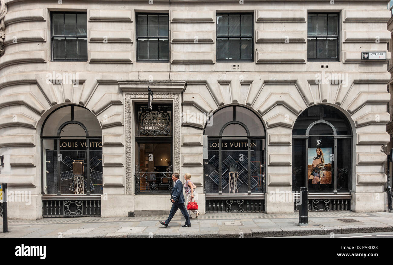 Pedestrians walking past the Louis Vuitton designer shop in Royal Exhange Buildings, Cornhill, London, England. Window display, designer bags. - Stock Image