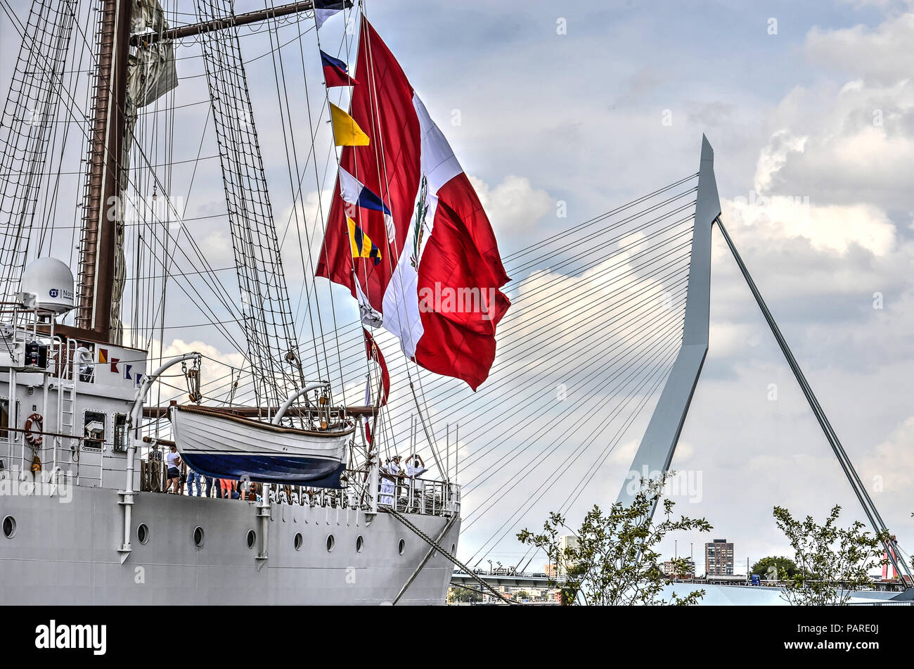 Rotterdam, The Netherlands, August 9, 2017: four-masted Peruvian navy ship Bap Union carrying large flag, moored at Wilhelminapier with Erasmusbridge  - Stock Image