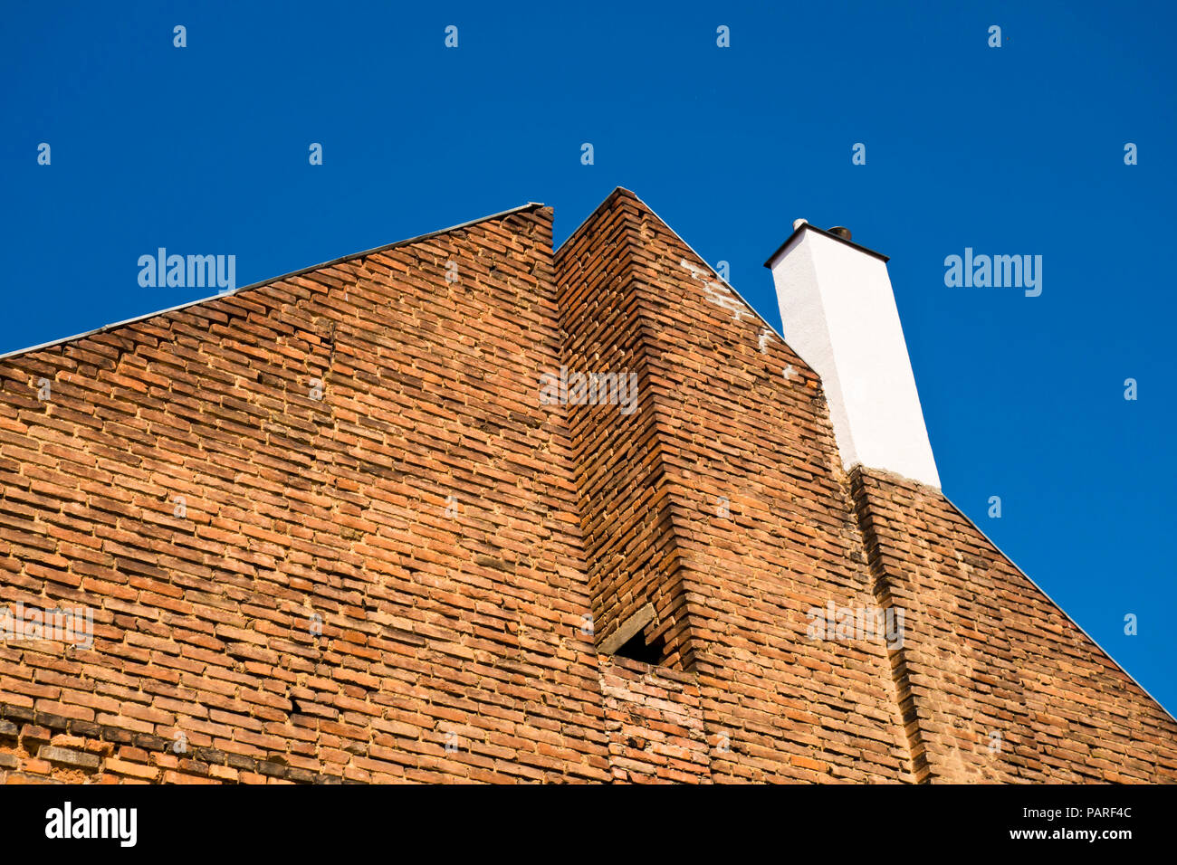 graphical angled view of a red bricks house with white chimney and blue sky - Stock Image