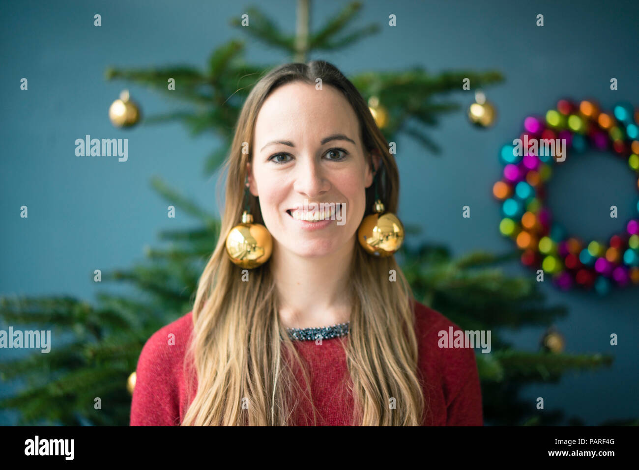 Portrait Of Smiling Woman Wearing Golden Christmas Baubles Earrings
