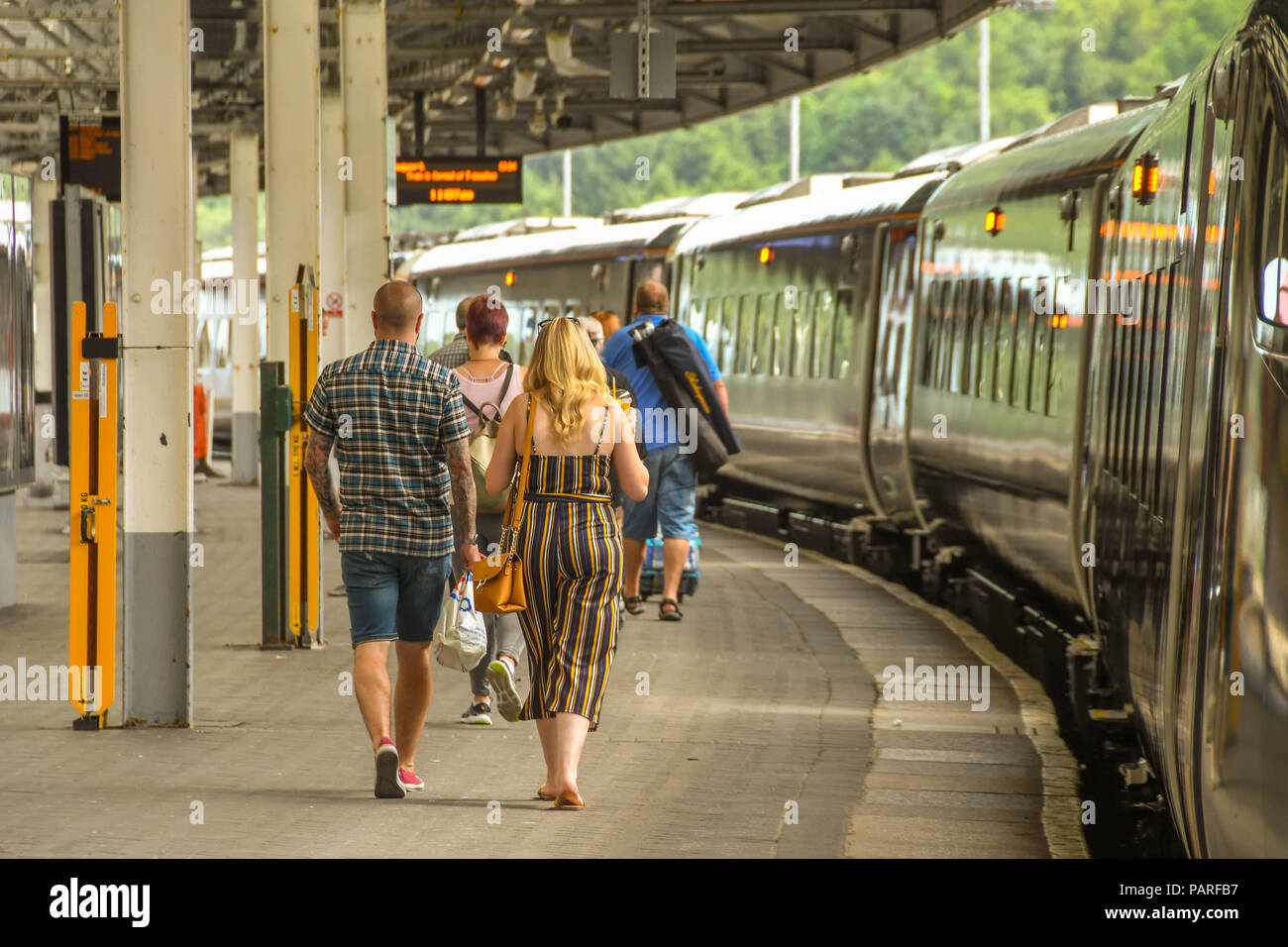 Passengers walking along a platform in Swansea station to board their train. Stock Photo
