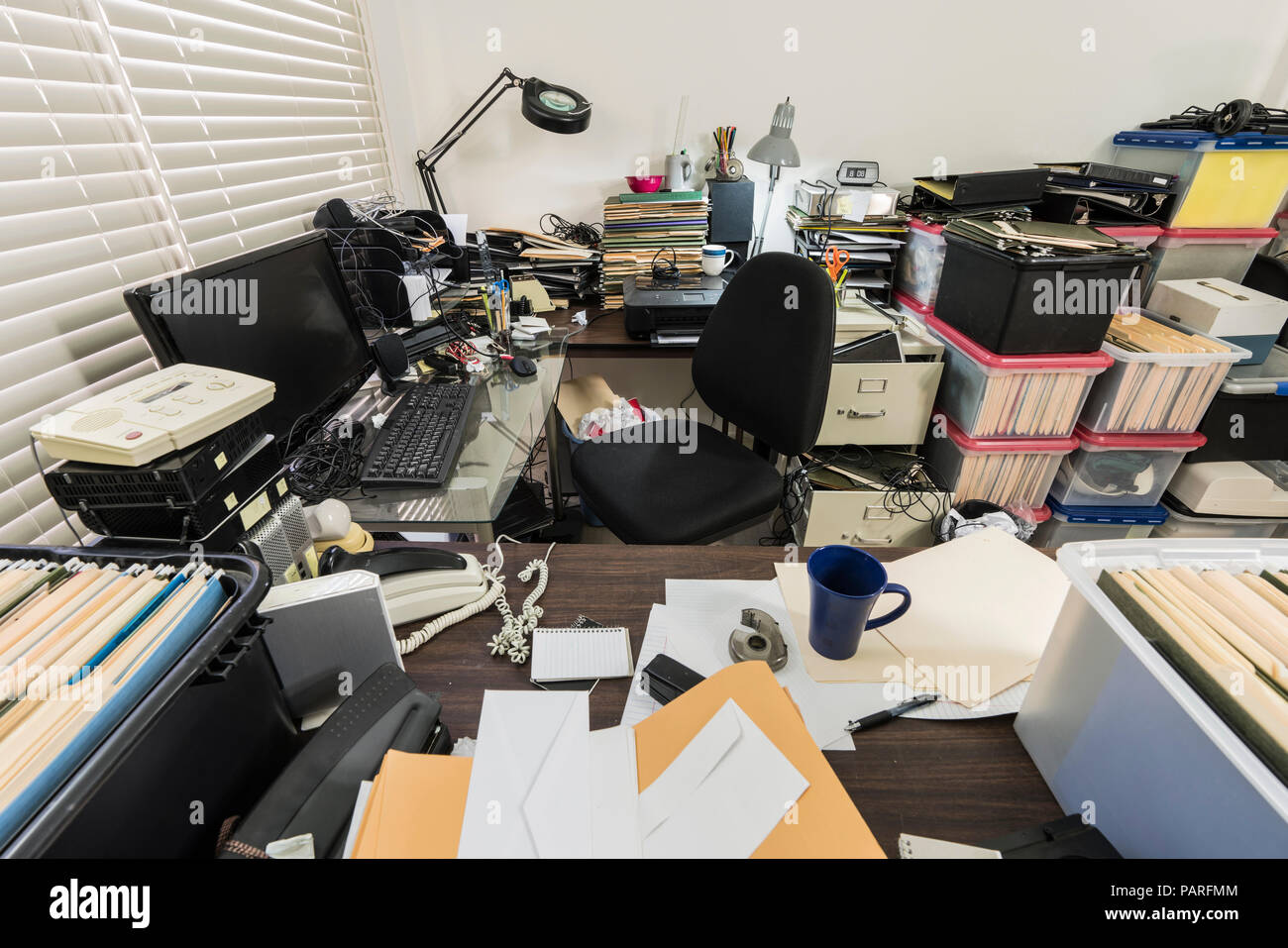 Messy business office with piles of files and disorganized clutter. - Stock Image