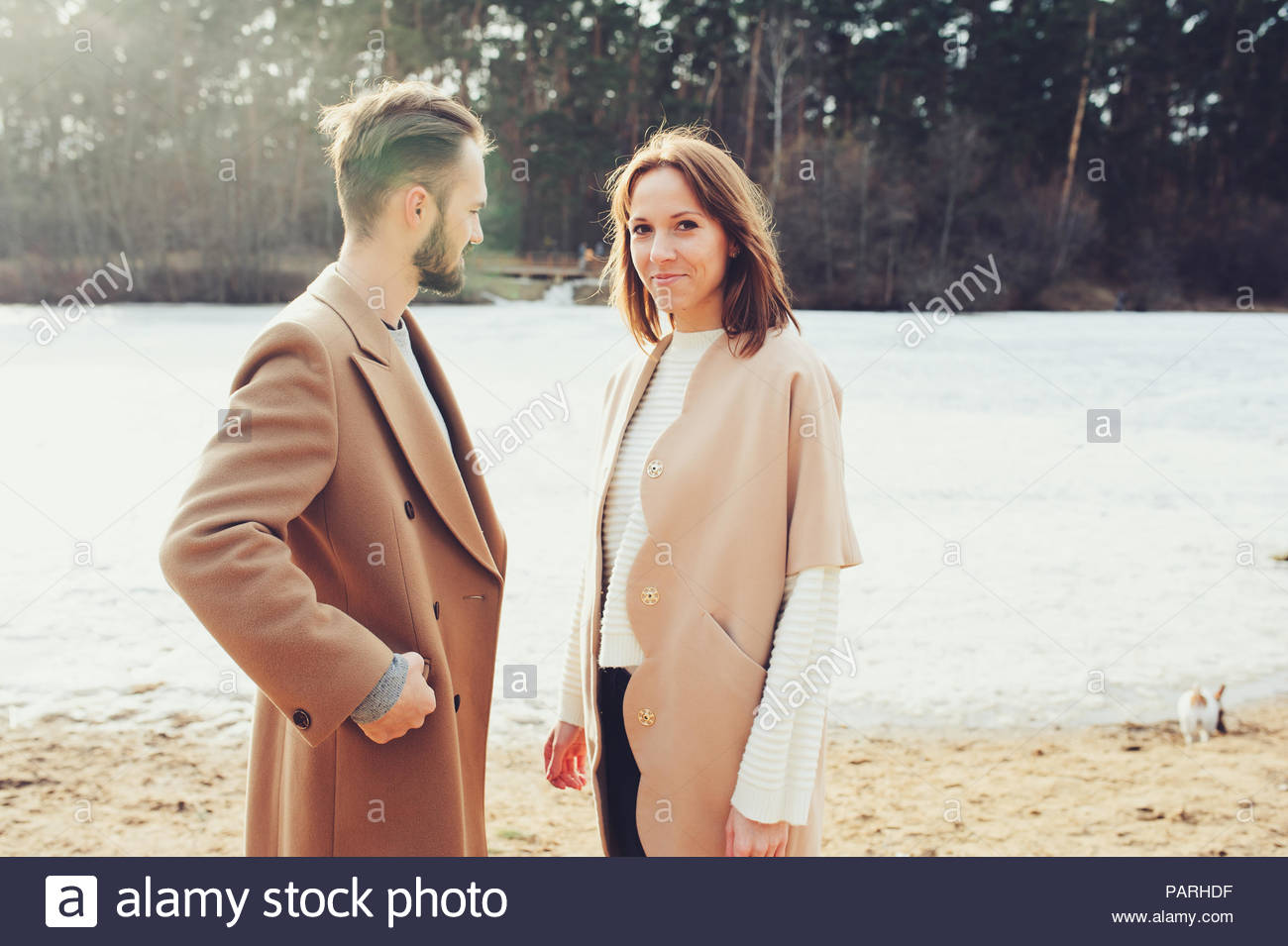 Three quarter length of a young couple standing at the beach - Stock Image