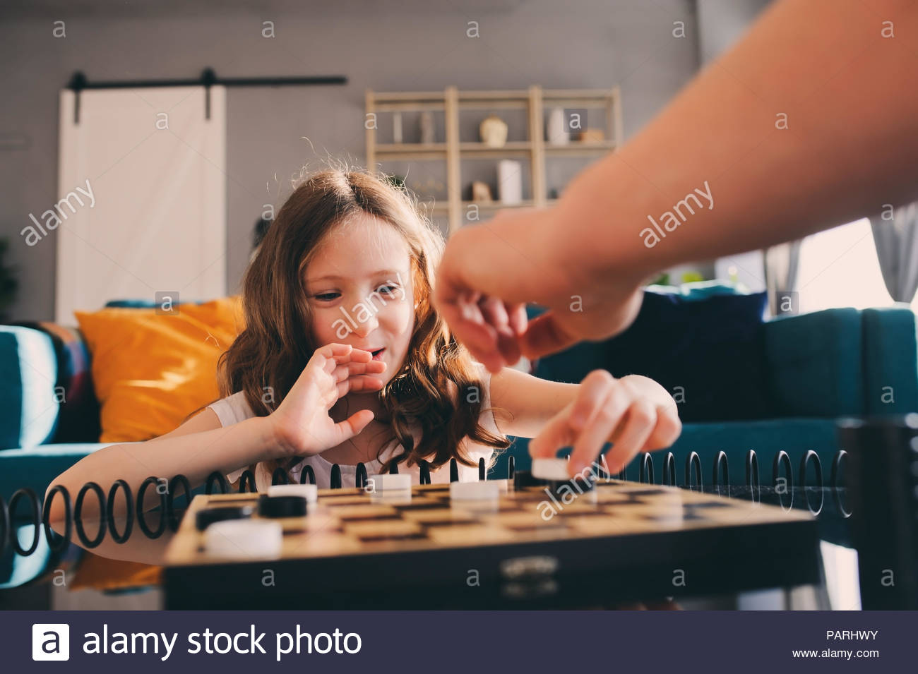 A young girl playing on the table at home - Stock Image