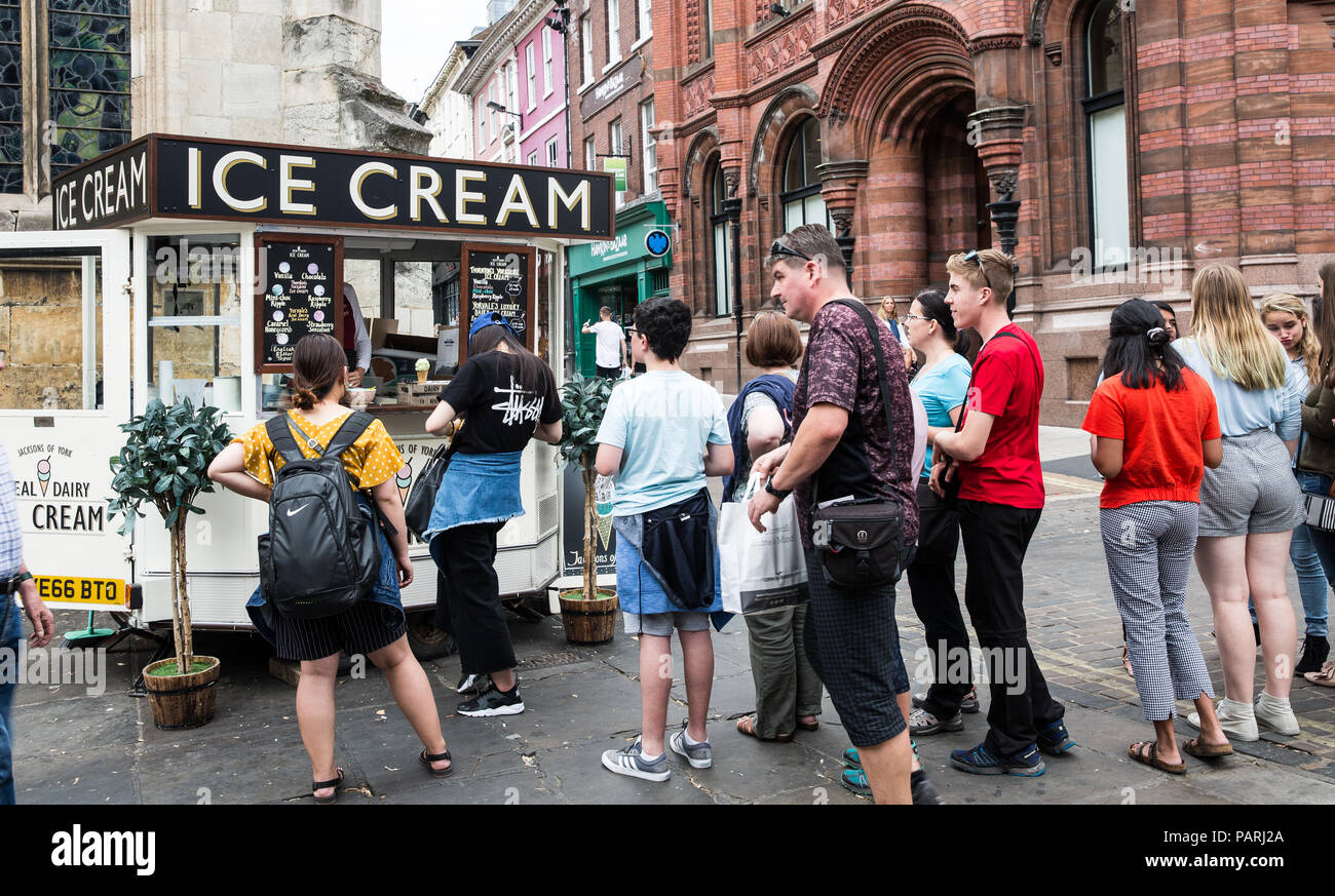 A long queue of people waiting in line at an old fashioned ice cream stand during a heatwave and hot weather in York, UK - Stock Image