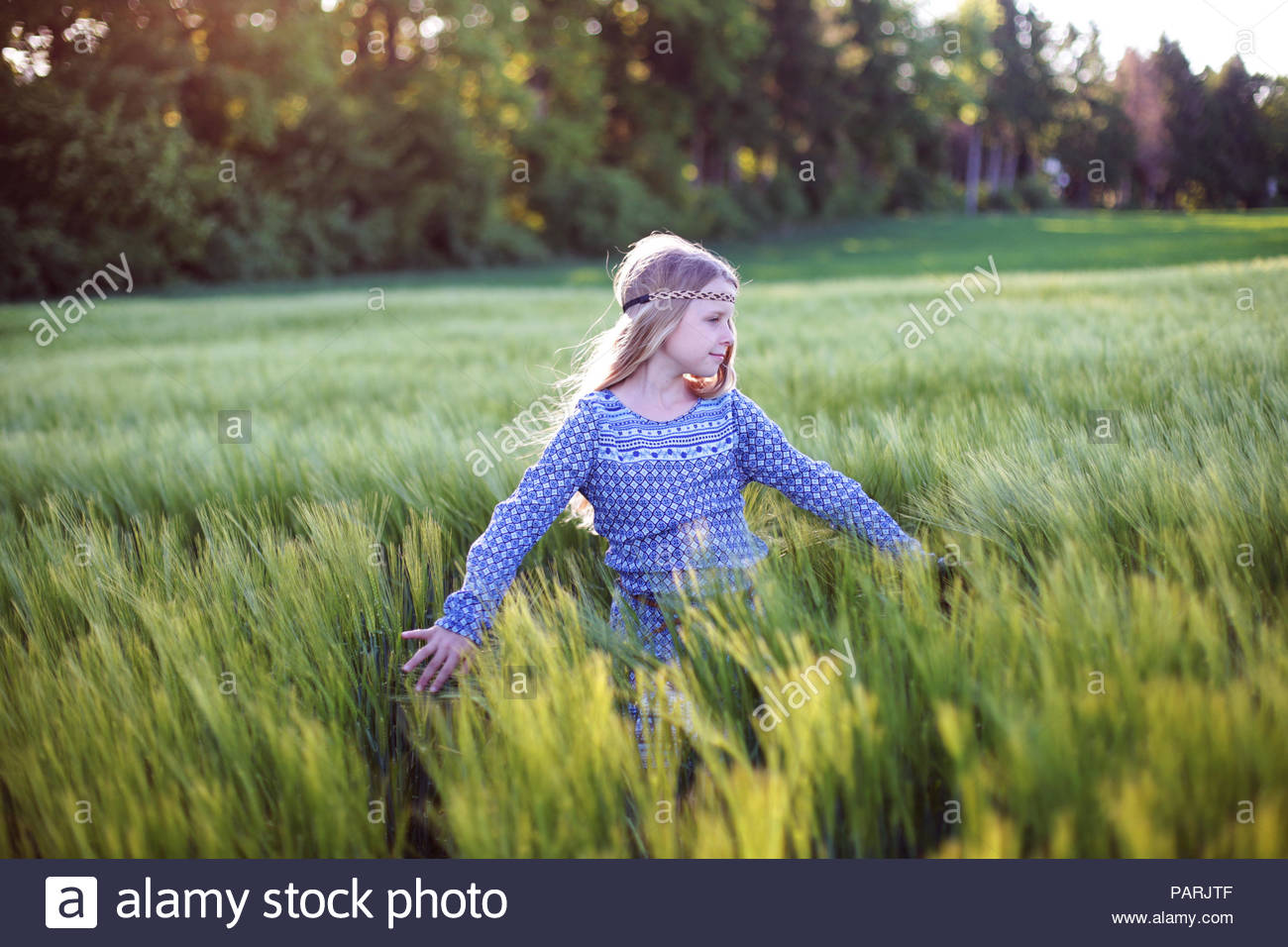 A young girl with blonde hair running in the grass - Stock Image