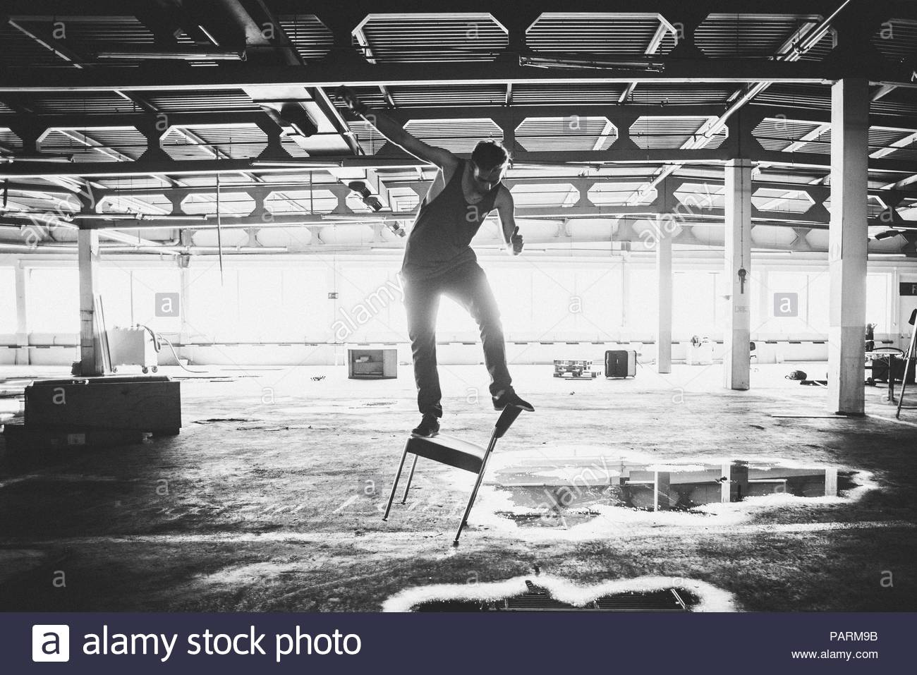 Man standing on balance on the top of a chair in an empty warehouse - Stock Image