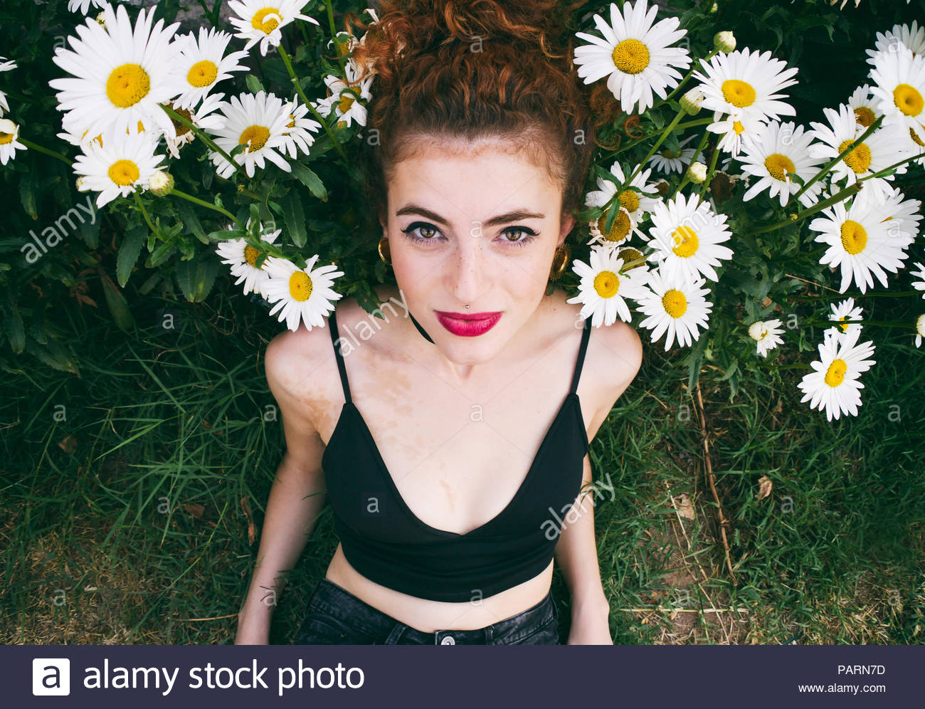 Portrait of young woman posing with daisies looking into camera - Stock Image