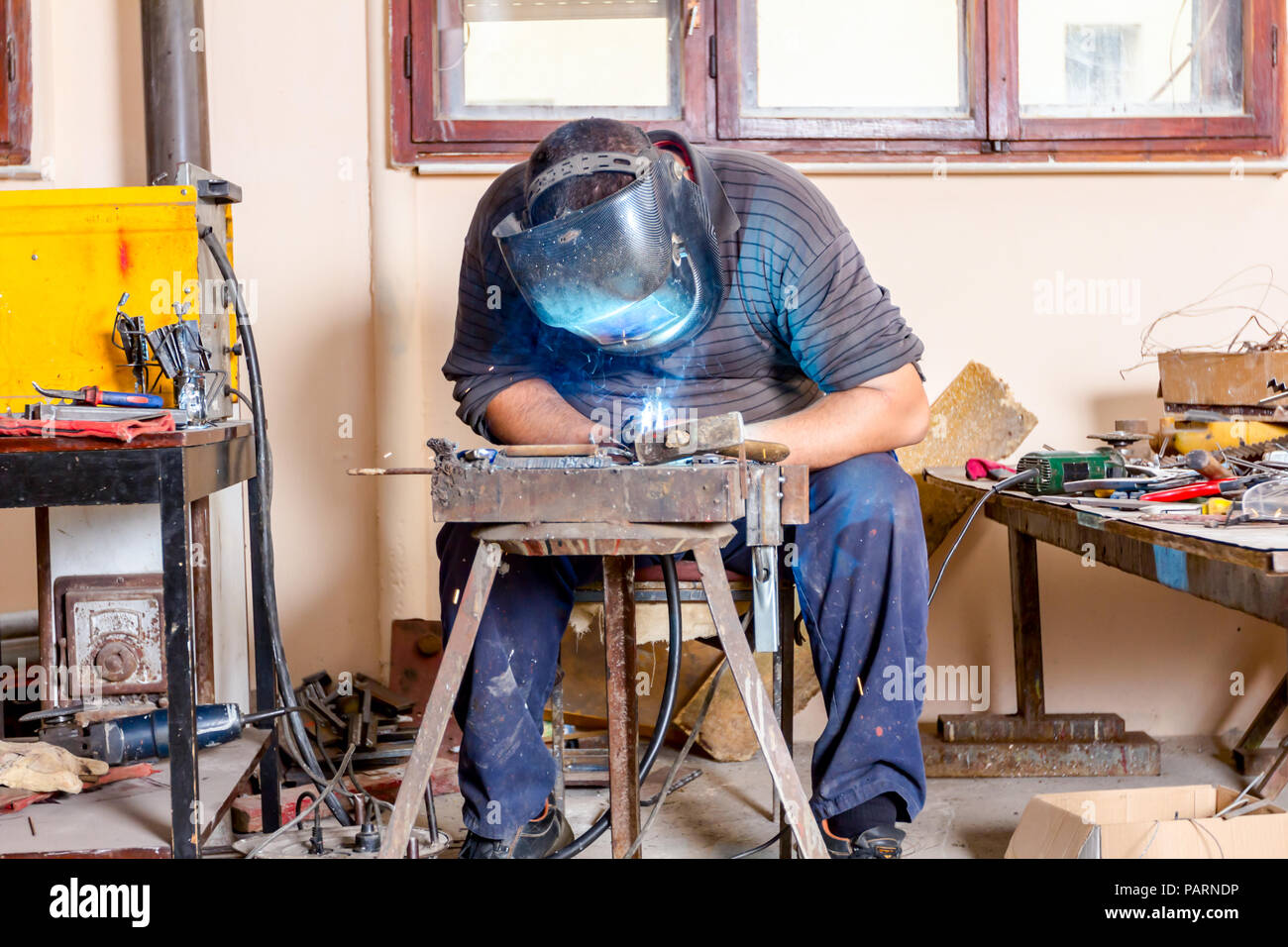 Sculptor is using arc welding to assembly metal sculpture barehanded with protective mask. Stock Photo
