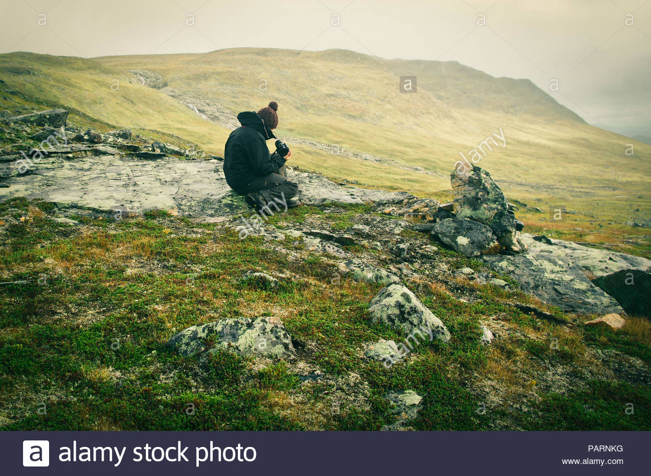 A man sitting on a rock in the mountains - Stock Image