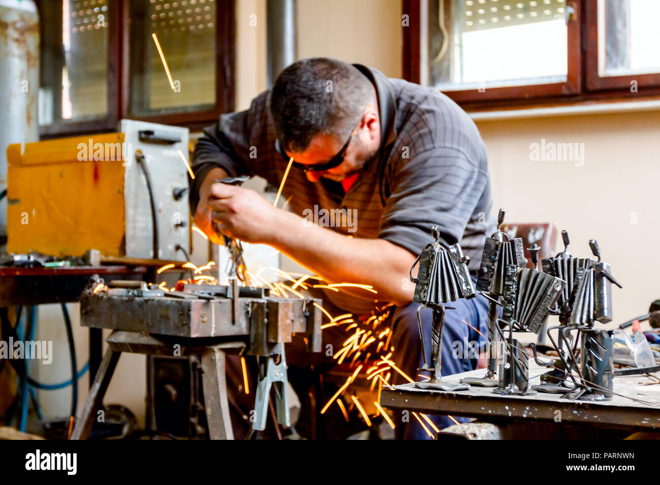 Sculptor is using arc welding to assembly metal sculpture barehanded with protective spectacles. - Stock Image