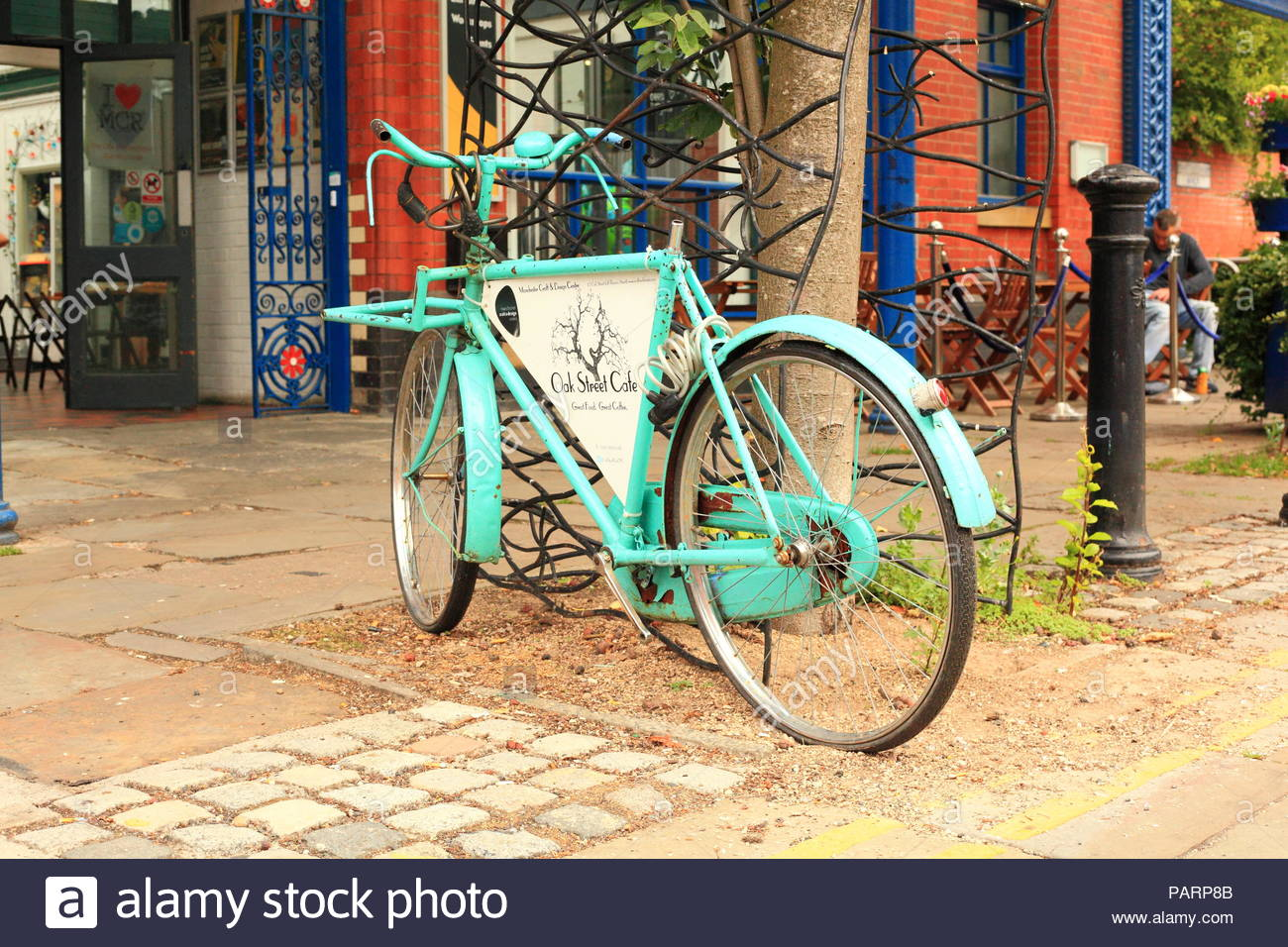 A quirky bicycle advertising the Oak Street Cafe at The Manchester Craft & Design Centre on Old Street. Northern Quarter, Manchester UK - Stock Image