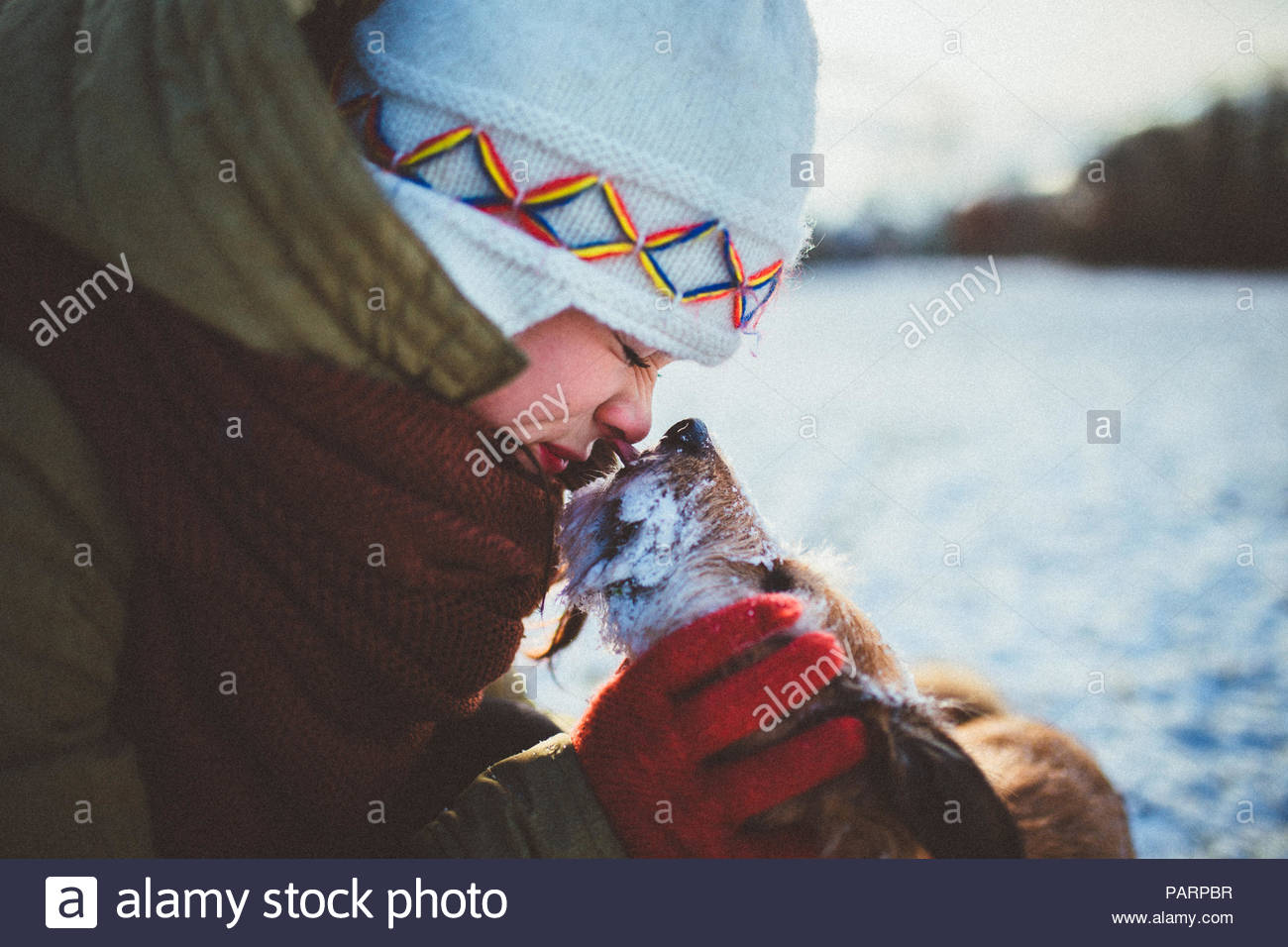 Woman with her cute pet dog in the snow - Stock Image