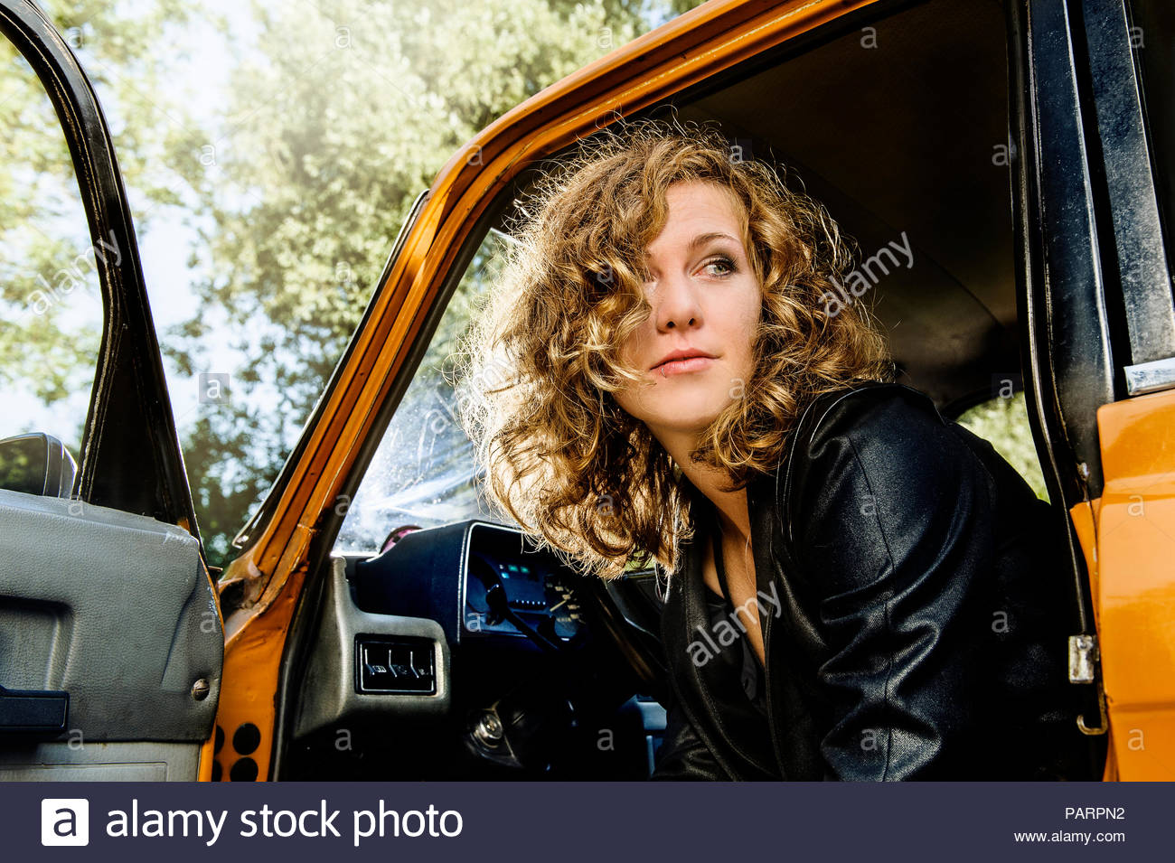 Portrait of a woman sitting in the car with the door opened - Stock Image