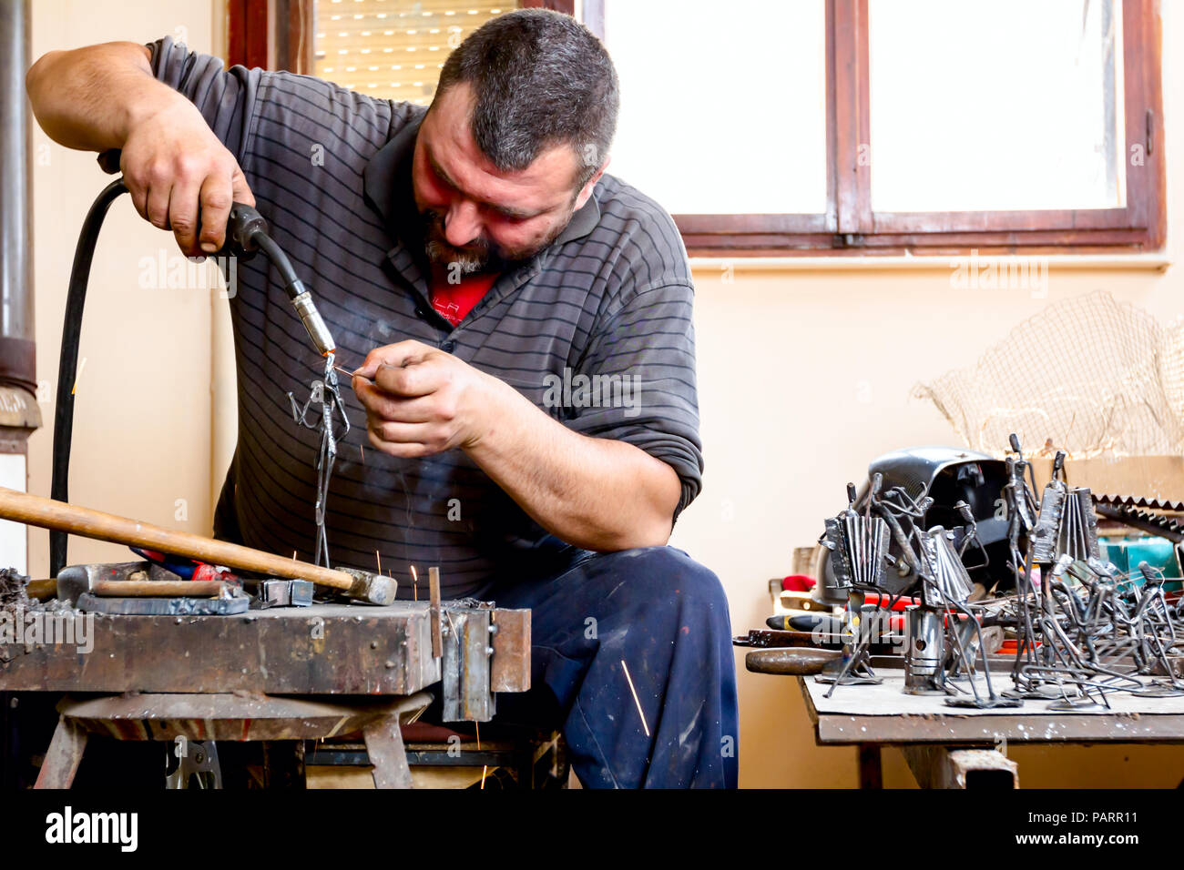 Sculptor is using arc welding to assembly metal sculpture without proper protection, barehanded. Stock Photo