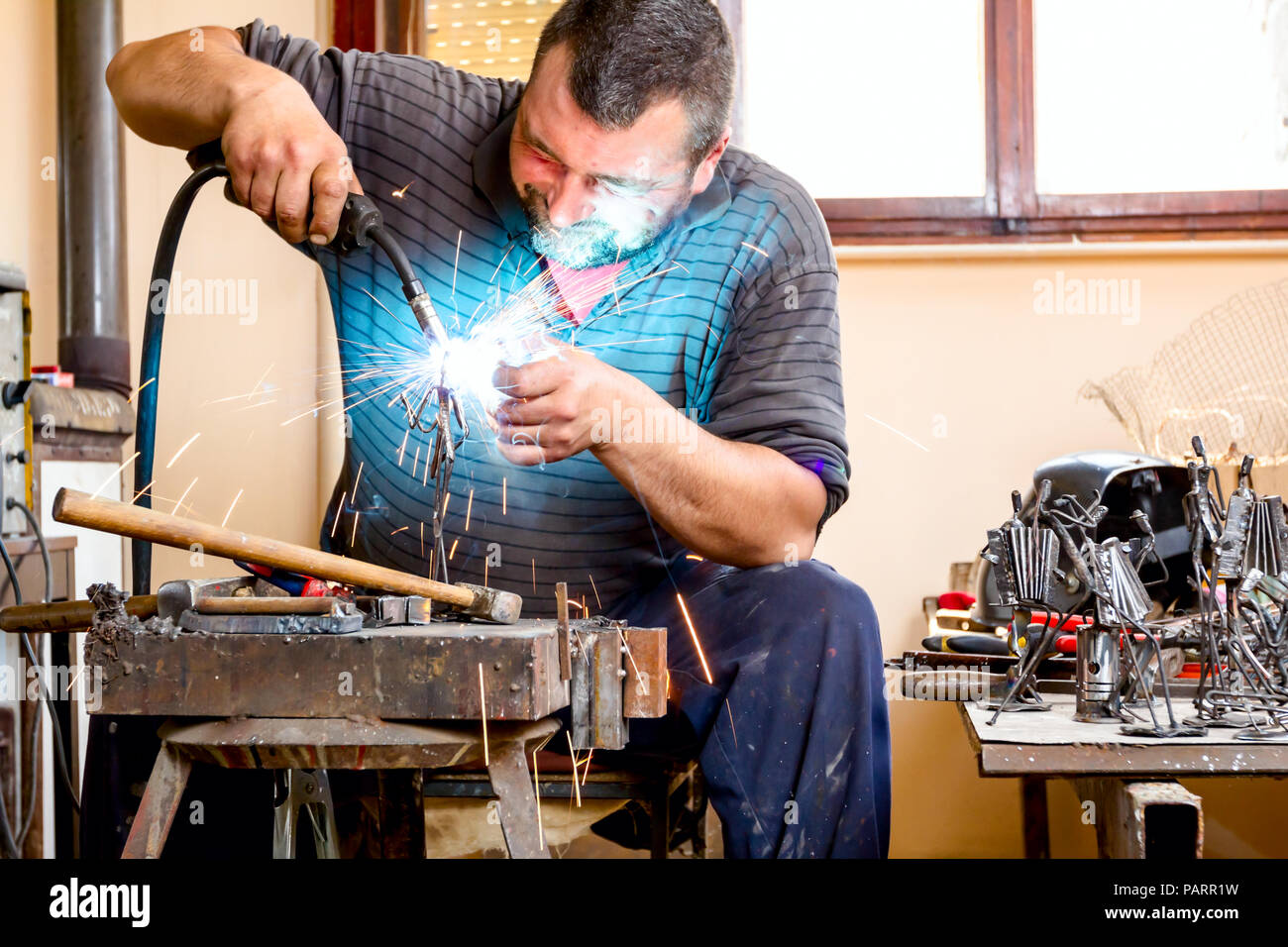 Sculptor is using arc welding to assembly metal sculpture without proper protection, barehanded. - Stock Image