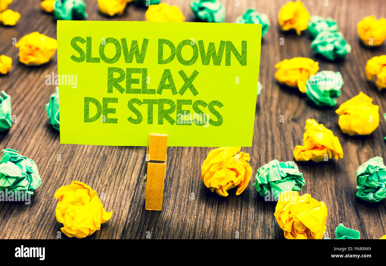 Handwriting text Slow Down Relax De Stress. Concept meaning Have a break reduce stress levels rest calm Paperclip retain written words yellow paper pa - Stock Image