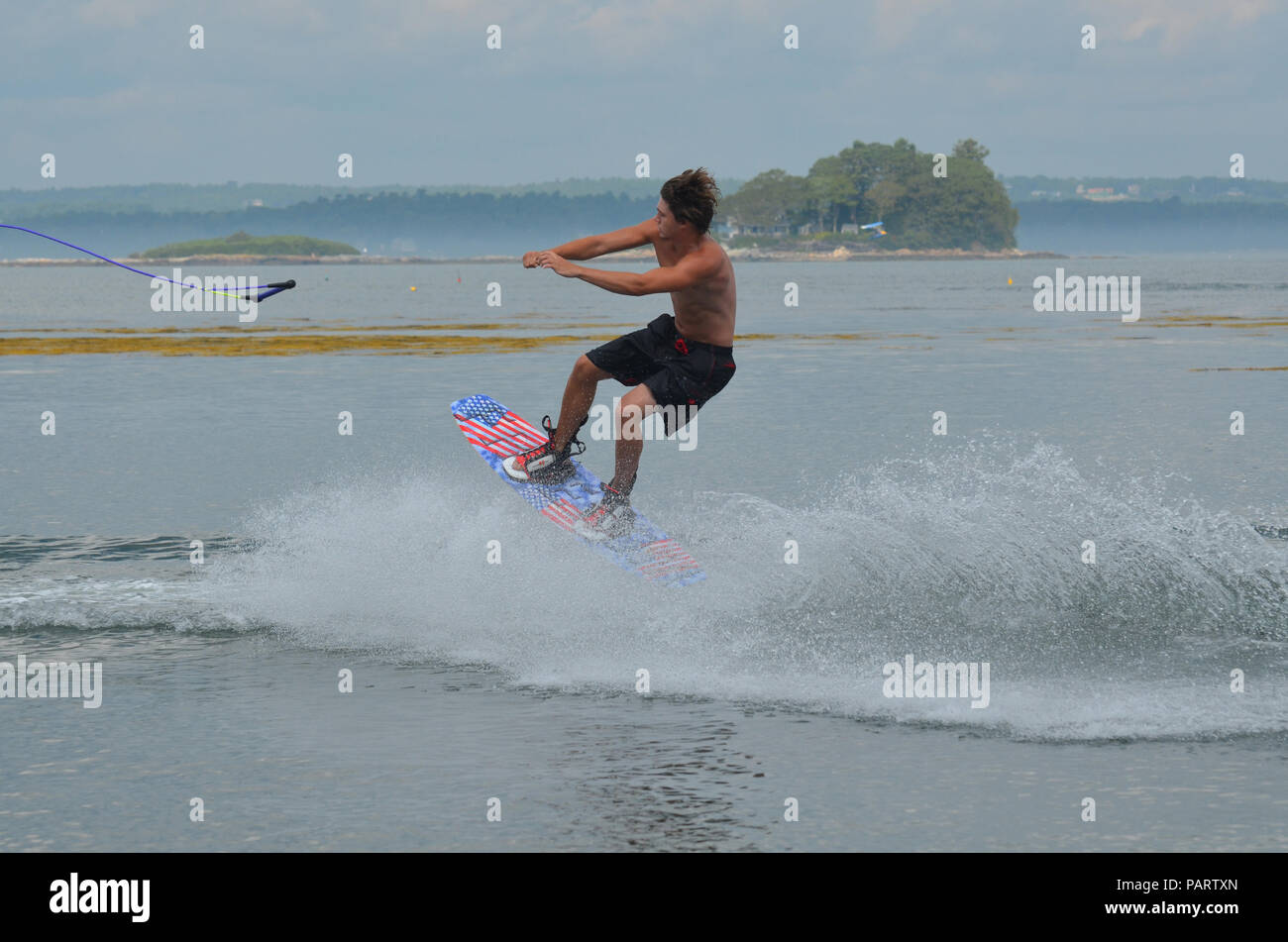 Wakeboarder letting go of the two rope while in the air. - Stock Image