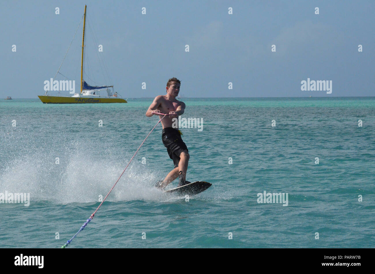 Young guy wakeboarding with black swim trunks off of Aruba. - Stock Image