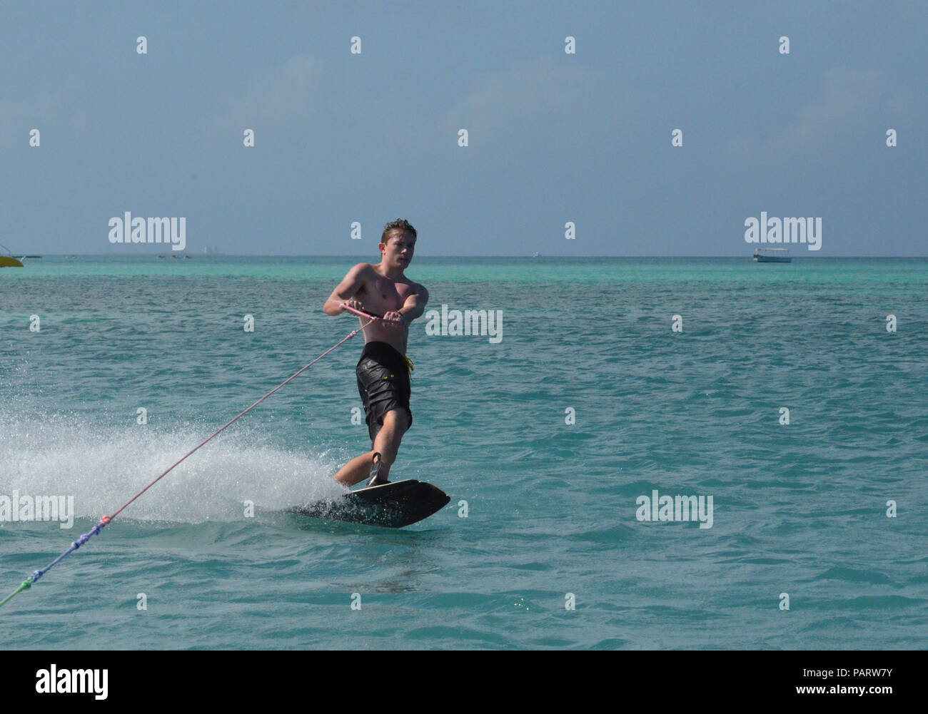 Young Aruba wakeboarder with black swim shorts in the water. - Stock Image