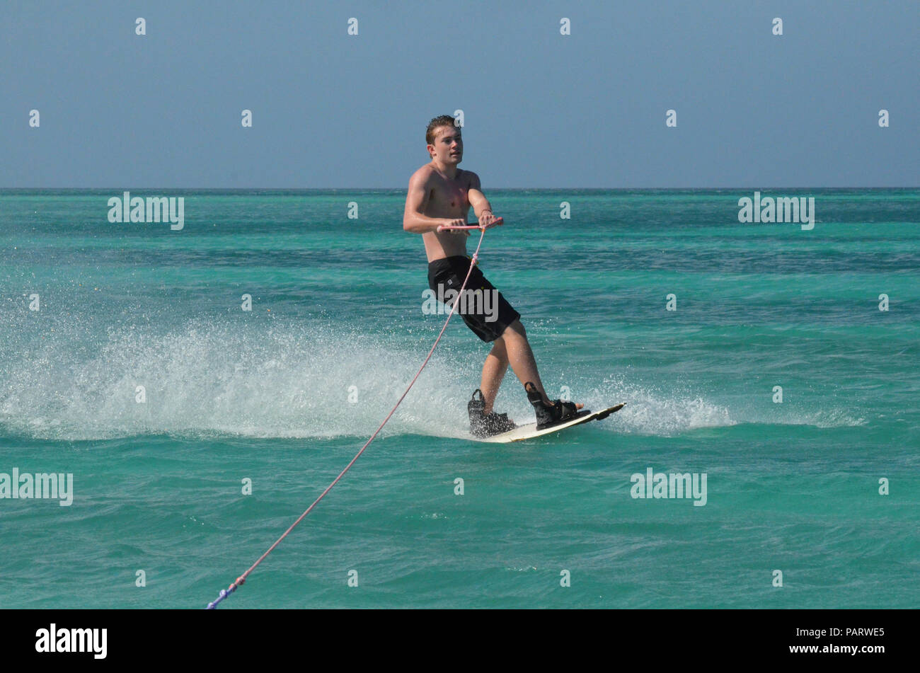 Wakeboarding young guy with black swim trunks in Aruba. - Stock Image