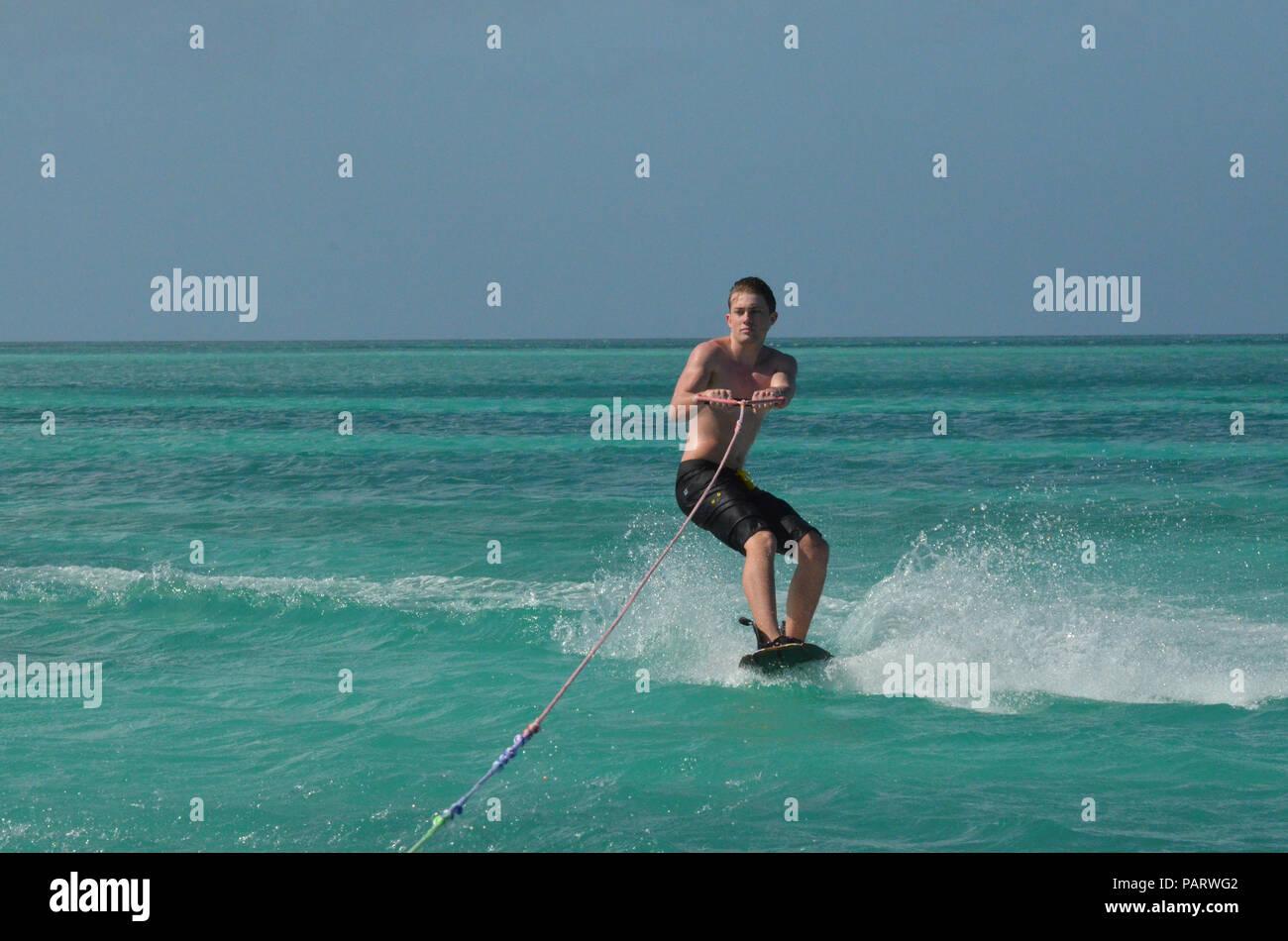 Wakeboarding guy in black swim trunks in Aruba. - Stock Image