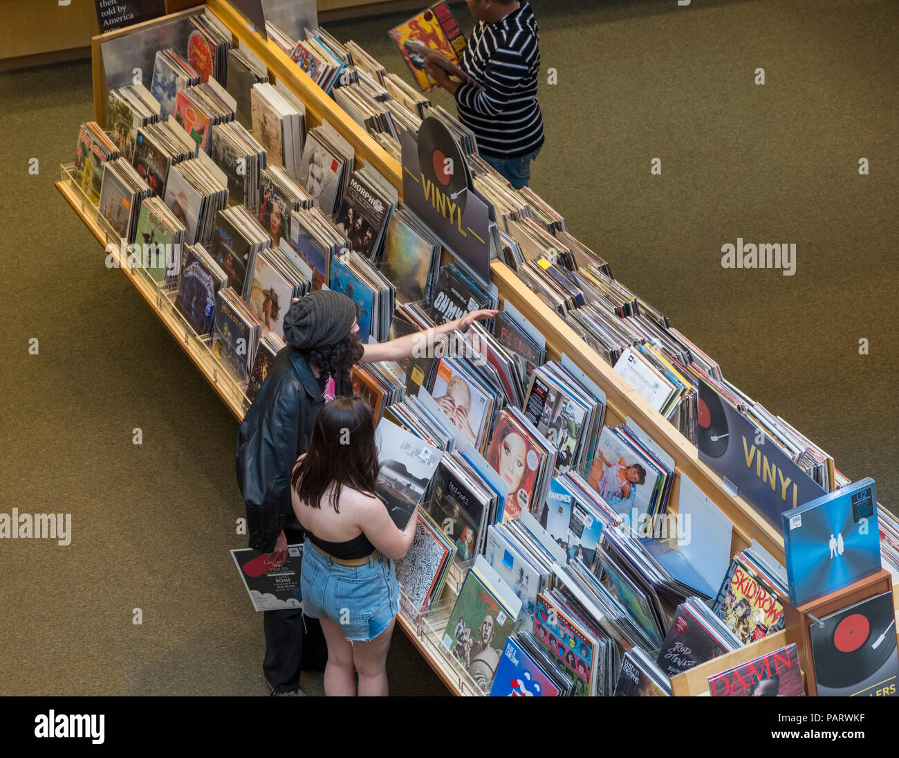 People browsing vinyl records and albums in racks at a record shop store interior in Los Angeles, LA, California, USA - Stock Image